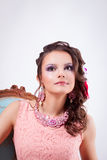 Woman with ornaments in the art soutache and bright makeup looki. Portrait of curly brunette with purple make-up in pink dress with soutache technique stock photo