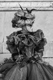 Woman in ornate costume, with mask and hat posing for the camera at the Church of San Giorgio Maggiore, Venice Italy. Woman in ornate costume, with mask and hat Stock Photography