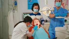 Dentistry doctor speaking to kid sitting on stomatological chair