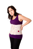 Woman with orthopedic body brace. Woman in pain from back injury wearing an orthopedic body brace corset, isolated Royalty Free Stock Photo