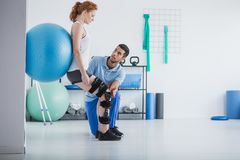 Woman with orthopedic problem exercising with ball stock photography
