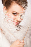 Woman with ostrich feather. Portrait of attractive young woman with makeup holding ostrich feather Stock Image