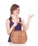 Woman with ostriches egg and wicker basket Stock Photo