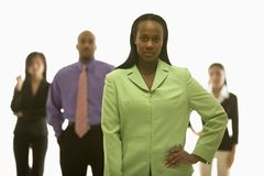 Woman with others. African-American businesswoman with hand on hip with others in background Stock Photos