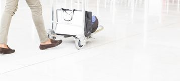 Woman our man walking suitcase luggage bag on trolley in the airport. royalty free stock photos