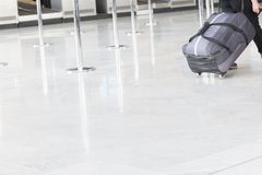 Woman our man walking suitcase luggage bag on trolley in the airport. royalty free stock images