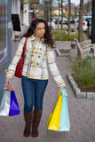 Woman Out Shopping the Town. A young Indian woman carrying colorful bags out shopping in the city Royalty Free Stock Images