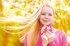 Woman outdoor. Beautiful young blond woman outdoor in the park with apple trees Royalty Free Stock Images