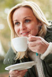 Woman In Outdoor Cafe With Hot Drink Royalty Free Stock Photo
