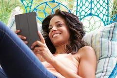 Woman On Outdoor Garden Swing Seat Using Digital Tablet Stock Photo