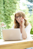 Woman outdoor with laptop and mobile phone. Shot of a beautiful middle aged woman making call and using laptop while sitting in the garden at home Royalty Free Stock Image