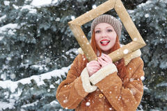 Woman outdoor portrait in wooden photo frame at winter season. Snowy weather in fir tree park. Stock Photography