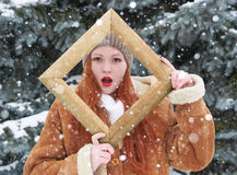 Woman outdoor portrait in wooden photo frame at winter season. Snowy weather in fir tree park. Royalty Free Stock Image