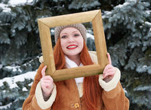Woman outdoor portrait in wooden photo frame at winter . Snowy weather in fir tree park. Royalty Free Stock Images