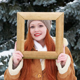 Woman outdoor portrait in wooden photo frame at winter . Snowy weather in fir tree park. Stock Photography