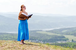 Red haired woman with book on the hilltop Royalty Free Stock Photos