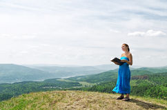 Red haired woman with book on the hilltop Royalty Free Stock Images