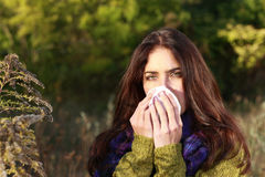 Woman outdoor sneezes her nose Royalty Free Stock Image