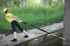 Woman on the outdoor suspension training. Fit woman on the outdoor suspension training at the water Stock Image