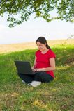 Woman Outdoor using laptop sitting on grass Royalty Free Stock Images