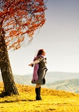 Young woman standing on an autumn hill.  stock photos