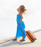 Young woman with suitcase on the pier Stock Photos