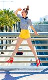 Woman outdoors in city looking into distance and jumping. Nosing around, having fun. Full length portrait of smiling stylish woman in yellow shorts and stripy Royalty Free Stock Images