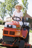 Woman outdoors driving lawnmower smiling Stock Image