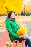 Woman outdoors enjoying the colorful autumn. Foliage sitting on a wooden park bench with a handful of bright yellow leaves smiling at the camera Royalty Free Stock Photography