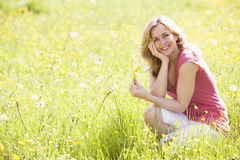 Woman outdoors holding flower smiling Stock Photos