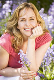 Woman outdoors holding flowers smiling royalty free stock photo