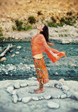 Heart Flowing Woman. Woman outdoors near a river with her arms and heart open in a mandala of stones Royalty Free Stock Photo