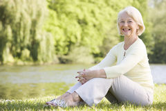 Woman outdoors at park by lake smiling Stock Photo