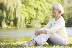 Woman outdoors at park by lake smiling Royalty Free Stock Image