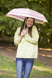 Woman outdoors in rain with umbrella smiling Stock Photography