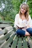 Woman outdoors reading Stock Images
