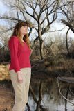 A Woman Outdoors on a River Bank Stock Images