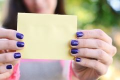 Woman outdoors showing a blank notepad. Stock Photos