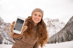 Woman outdoors among snow-capped mountains showing cell phone Stock Photography