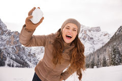 Woman outdoors among snow-capped mountains throwing snowball Stock Photography