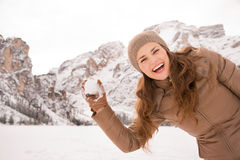 Woman outdoors among snow-capped mountains throwing snowball Stock Images