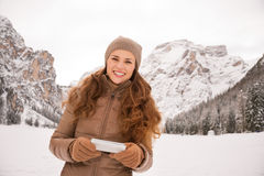 Woman outdoors among snow-capped mountains writing sms Royalty Free Stock Photography