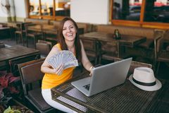 Woman in outdoors street coffee shop cafe sitting with modern laptop pc computer, hold in hand bunch of dollars stock photo