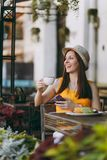 Woman in outdoors street coffee shop cafe sitting at table in hat with cup of cappuccino cake, using mobile phone