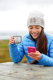 Woman outdoors using smart phone drinking coffee Royalty Free Stock Photo