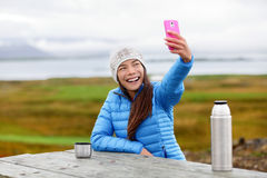 Woman outdoors using smart phone taking selfie Royalty Free Stock Images