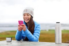 Woman outdoors using smartphone drinking coffee Stock Photos