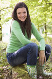 Woman outdoors in woods sitting on log smiling royalty free stock image