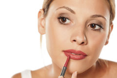 Woman outlining her lips. Young beautiful woman outlining her lips with a pencil Stock Image