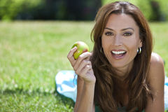 Woman Outside Eating An Apple & Smiling Stock Photos